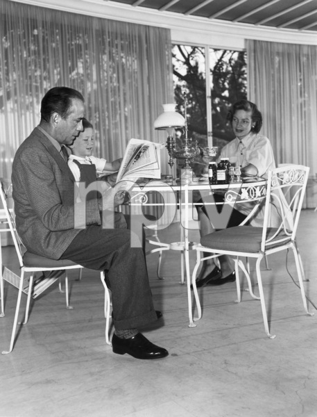 Humphrey Bogart at home reading the newspaper with his son, Stephen, and wife Lauren Bacall1952© 1978 Sid Avery - Image 0015_0032