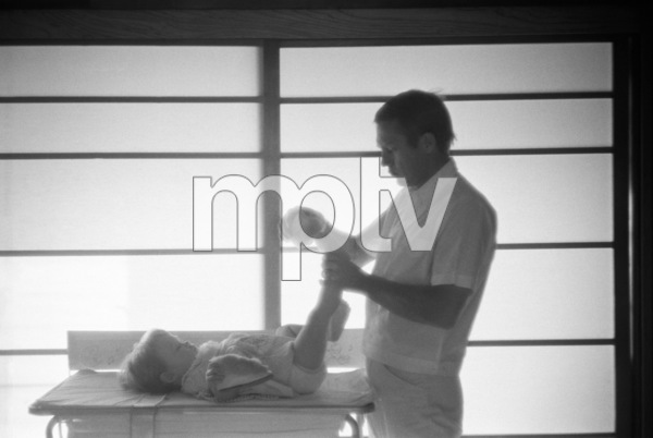 Steve McQueen putting slippers on daughter Terry at their Hollywood Hills home on Solar Drive1960© 1986 Sid Avery - Image 0019_0006