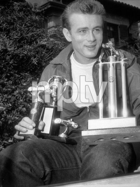 James Dean shown with a trophy hewon in a recent auto race before