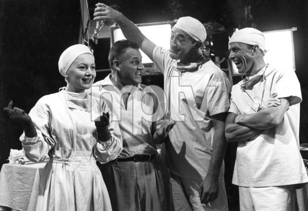 "Dir. Stanley Kramer, Olivia De Havilland, Frank Sinatra, and Robert Mitchum on the set of ""Not As A Stranger,"" 1954. © 1978 Sid Avery - Image 0077_0001"