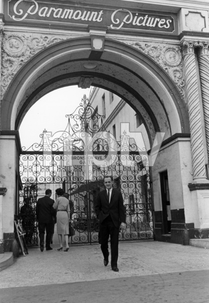 Bob Newhart in front of the Bronson Gate at Paramount Studios1961 © 1978 Sid Avery - Image 0092_0933