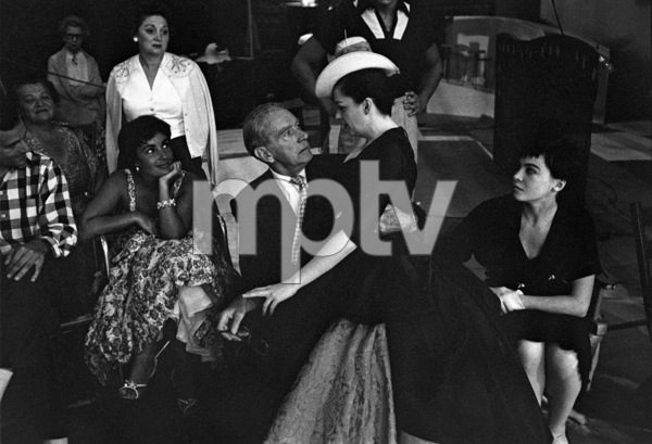 Elizabeth Taylor watches as Judy Garland sits on Clifton Webb