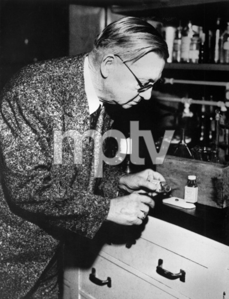 Coroner looking at bottle of sleeping pills which caused the death of Lupe Velez1944 - Image 0725_0039