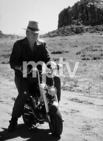 "John Wayne riding a motorcycle on location for ""Big Jake,"" National General 1970. © 1978 David Sutton - Image 0898_0836"