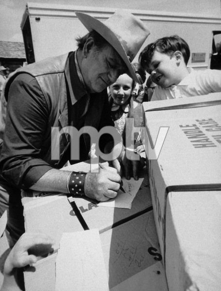 "John Wayne signing autographs on location for ""The Cowboys,"" Warner Bros. 1971. © 1978 David Sutton - Image 0898_0843"
