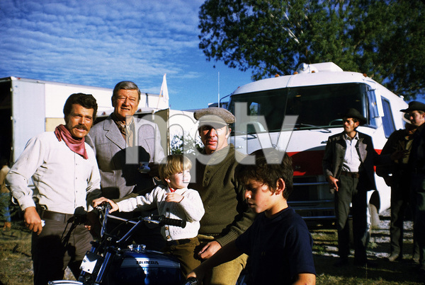 """John Wayne with his sons, Patrick and Ethan, and his grandson, Ian, during a break from filming """"Big Jake,"""" Batjac/Cinema Center 1970. © 1978 David Sutton - Image 0898_3048"""