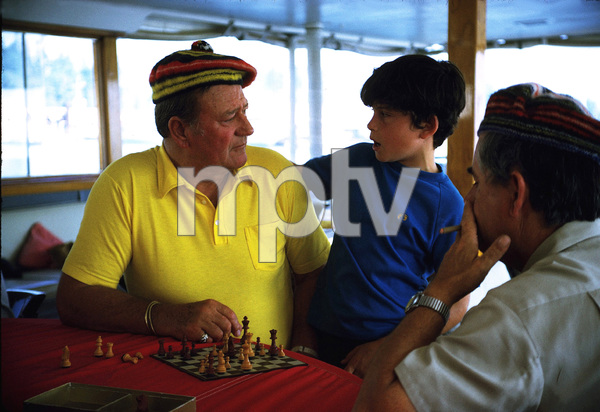 """John Wayne playing chess with his son, Ethan, and skipper, Jack Headley, on his yacht, """"Wild Goose,"""" 1971. © 1978 David Sutton - Image 0898_3088"""