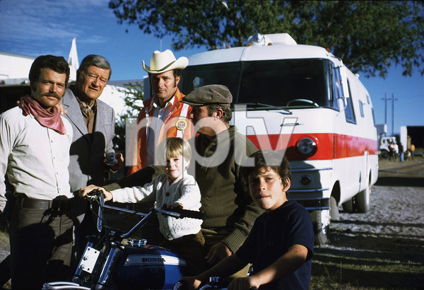 """John Wayne with his sons, Patrick, Michael, and Ethan, and his grandson, Ian, during a break from filming """"Big Jake,"""" Batjac/Cinema Center 1970. © 1978 David Sutton - Image 0898_3107"""
