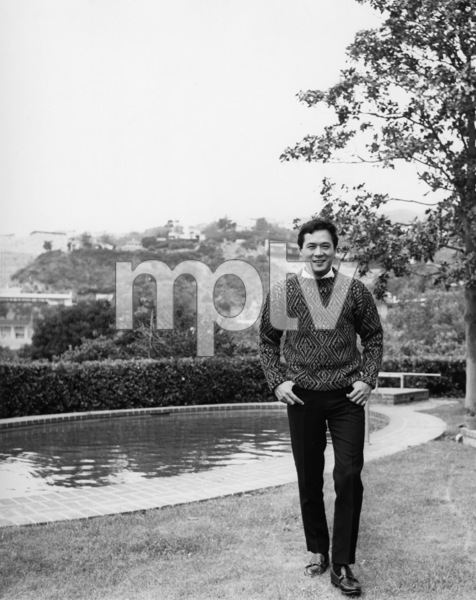 James Shigeta walking beside pool at his Georgian-Colonial home on top of the Hollywood Hillscirca 1956Photo by Joe Shere - Image 21096_0007