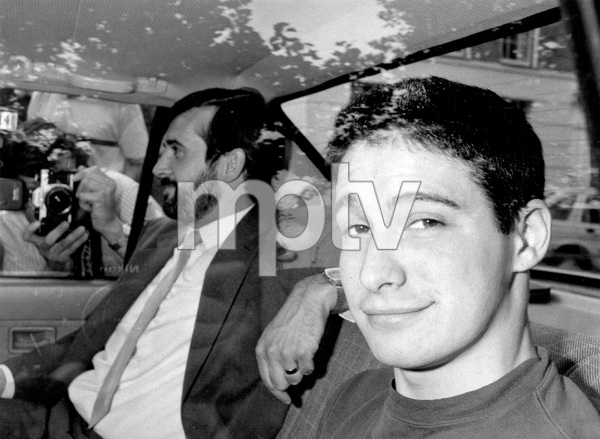 """BEASTIE BOYS, Adam Horovitz leaves Liverpool with police escort after being arrested for """"grievious bodily harm after a riot at his rock concert"""" -- Earlier he was in tears after being arrested but soon was back in form, snarling at reporters, mouthing obscenities and giving the defiant finger, 1987, I.V. - Image 22727_0021"""