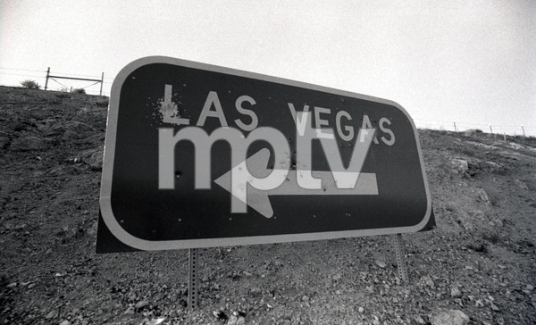 """Poker Face""A sign in the Nevada desert full of bulletholes.  Not clear if Las Vegas losers leaving Las Vegas or ones on the way to town, feeling lucky and letting off a few shots1980 © 1980 Ulvis Alberts - Image 22802_0001"