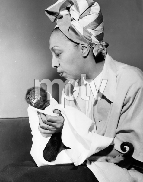 """Josephine Baker with her pet spider monkey, """"BINKI"""" who is suffering from a cold.  Ms. Baker arrived in NY for an engagement and BINKI is part of the show, 1951, I.V. - Image 23423_0017"""