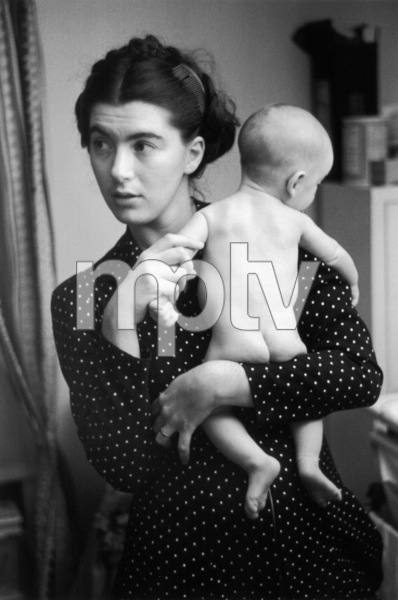 A young mother, wearing a polka-dotted dress, holds her naked infant in her arms, New York City1947© 1978 Ruth Orkin - Image 24388_0037