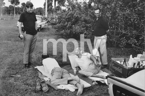 John F. Kennedywith Charles Spalding (roommate at Harvard), Prince Stanislas Radziwill, Dr. Max Jacobson (standing) after a 50 mile hike down the Sunshine Parkway towards Miami, Florida / 1963 © 2000 Mark Shaw - Image 2554_0131