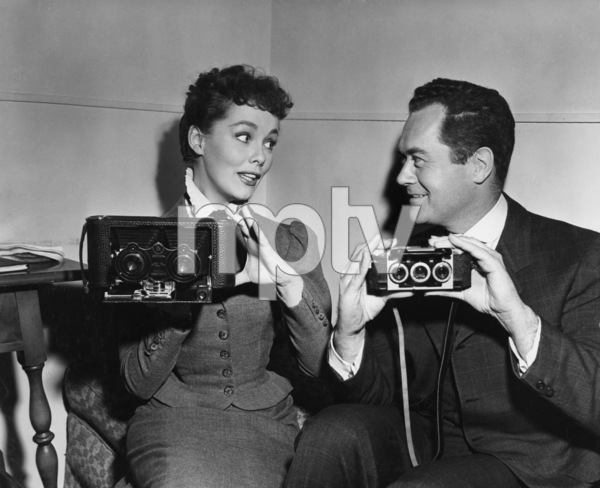"Frank Lovejoy and Phyllis Kirk compare an old-type stereoptican still camera with a present-day model on the set of ""House of Wax"" (the camera held by Miss Kirk is a 1902 Kodak, one of the first stereo cameras made.  The one held by Lovejoy is the new Stereo-Realist)1953Photo by Jack Woods - Image 2619_0001"
