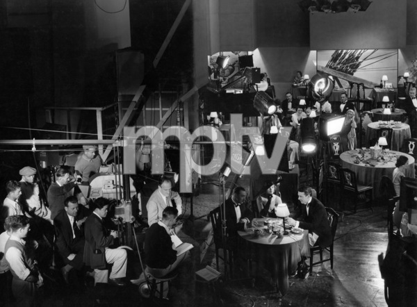 """Stamboul Quest""Myrna Loy, George Brent, director Sam Wood (sitting in front of the camera), cinematographer James Wong Howe (behind the camera in white trousers)1934 MGMPhoto by Ted Allan - Image 4280_0005"