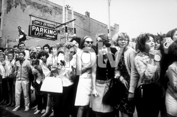 Beatles Fans lined up by the sidewalkanxious to get a glimpse of the Beatles,1964 © 1978 Gunther / MPTV  - Image 7685_0166