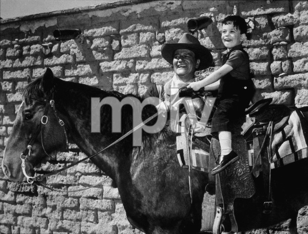 """John Wayne with his son, John Ethan, 3, on location near Durango, Mexico for the film """"The Sons of Katie Elder"""" 1965 Paramount Pictures - Image 9030_0006"""
